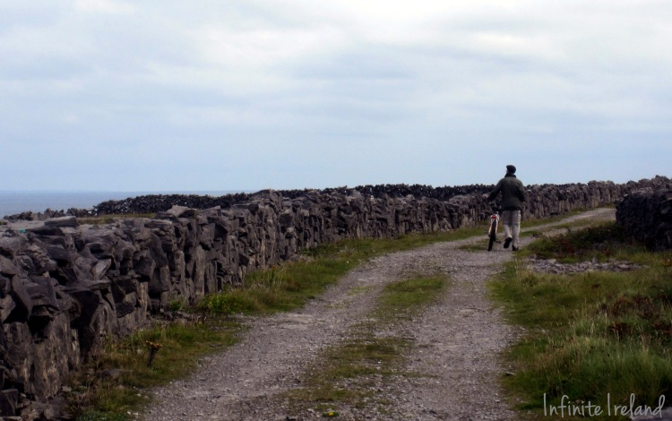 Walking a bike on Inis Mor's back roads lined with stone walls