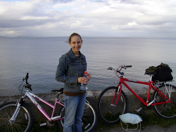 Woman with two bikes and ocean