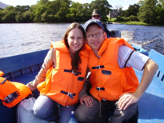Man, Woman with life jackets and Boat Driver on small motor boat