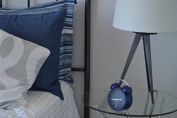 blue alarm clock on table beside bed