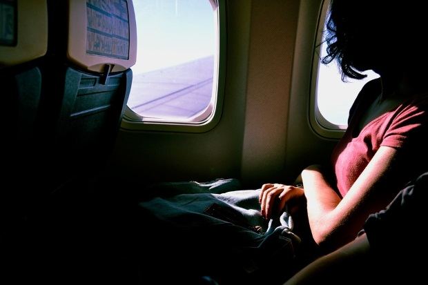 Woman looking out airplane window over wing