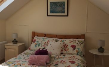 Double Bed with flower blanket, pillows and pink towels at AirBnB. Wing it in Ireland