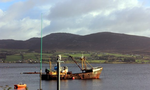Ireland mountains and bay with old fishing boat