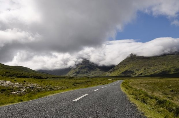 Rural Road in Ireland surrounded by mountain and clouds