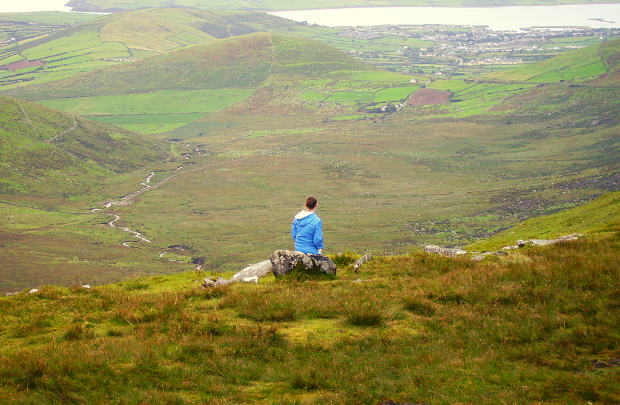 Woman on rock overlooking Dingle Peninsula on Conor Pass